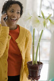 Black woman on cell phone admiring a flower. Smiling beautiful African American woman talking on a cell phone holding a flowering plant Stock Images