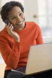 Black woman on cell phone with laptop royalty free stock photo
