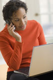 Black woman on cell phone and laptop Stock Images