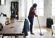 Black woman cleaning room alone Stock Photo