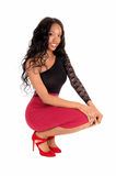 Black woman crouching on floor. A lovely African American woman in a red skirt and black blouse crouching Stock Images