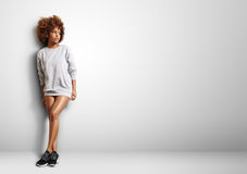 Black woman with curly hair wearng sweatshirt like a dress. In studio Stock Image