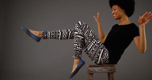 Black woman dancing on chair Stock Image