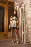 Black woman in denim dress standing by entrance Royalty Free Stock Photography