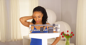 Black woman disappointed after checking weight Stock Images