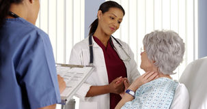 Black woman doctor holding elderly patient's hand in hospital room Royalty Free Stock Photos