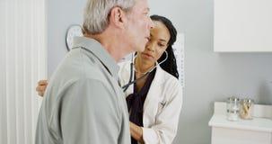 Black woman doctor listening to senior breathing Stock Photo