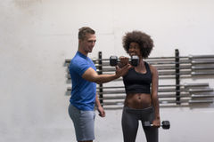 Black woman doing bicep curls with fitness trainer Stock Photography