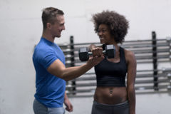 Black woman doing bicep curls with fitness trainer Royalty Free Stock Images