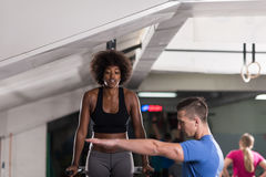 Black woman doing parallel bars Exercise with trainer. African american athlete women workout out arms on dips horizontal parallel bars Exercise training triceps Royalty Free Stock Images