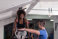 Black woman doing parallel bars Exercise with trainer. African american athlete women workout out arms on dips horizontal parallel bars Exercise training triceps Royalty Free Stock Photography