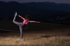 Black woman doing yoga  in the nature. Young beautiful black woman doing yoga exercises in the nature of a beautiful summer night Royalty Free Stock Photo