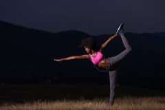 Black woman doing yoga  in the nature. Young beautiful black woman doing yoga exercises in the nature of a beautiful summer night Stock Photography