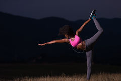Black woman doing yoga  in the nature. Young beautiful black woman doing yoga exercises in the nature of a beautiful summer night Stock Image