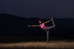 Black woman doing yoga  in the nature. Young beautiful black woman doing yoga exercises in the nature of a beautiful summer night Stock Photo