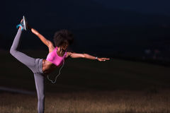 Black woman doing yoga  in the nature. Young beautiful black woman doing yoga exercises in the nature of a beautiful summer night Royalty Free Stock Image