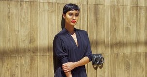 Black woman in dress leaning against wall Stock Photo