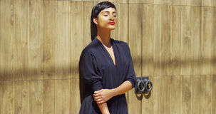 Black woman in dress leaning against wall and enjoying sun light Stock Photography