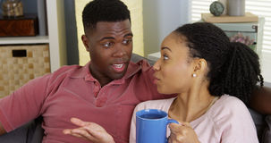 Black woman drinking tea and chatting with boyfriend on couch Royalty Free Stock Photo