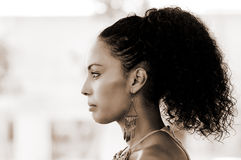 Black woman with earrings. Afro hairstyle. Portrait of a young black woman profile, model of fashion, with pink dress and earrings. Afro hairstyle Stock Images