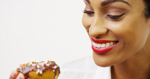 Black woman eating chocolate donut with sprinkles and smiling Royalty Free Stock Photo