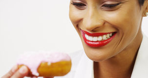 Black woman eating donut with pink frosting and smiling Royalty Free Stock Photography
