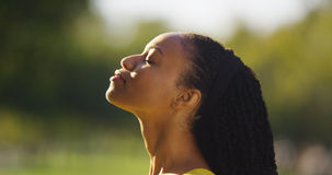 Black woman feeling the sun shine on her face Stock Images