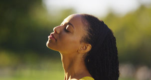 Black woman feeling the sun shine on her face. Outdoors royalty free stock photography