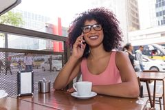 Black woman with frizzy hair using cell phone outdoors and having a cup of coffee in Sao Paulo during summer, urban background. royalty free stock image