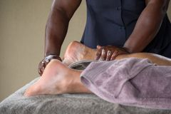Black woman gives a foot massage to an elderly Caucasian man. Black woman gives a relaxing foot massage to an elderly Caucasian man at a health spa in South royalty free stock photos