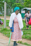 Black woman with green umbrella walking through Zulu village in Zululand, South Africa Stock Photo