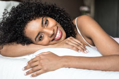 Black woman happy on bed smiling and stretching looking at camer Royalty Free Stock Images