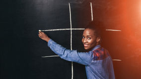 Black woman have fun playing tic tac toe on wall. Woman Black Play Tic Tac Toe Game Fun Entertainment Afroamerican Happy Childhood Early Brain Development Royalty Free Stock Photo