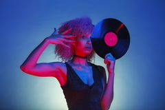 Black woman holding a retro vinyl with eighties disco music royalty free stock photography