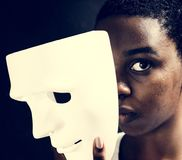 Black woman holding a white mask Royalty Free Stock Image