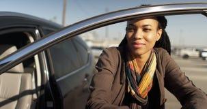 Black woman leaning against car door in parking lot. Medium Close up of Black woman leaning against car door in parking lot Stock Photography