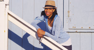 Black woman leaning on wooden rail smiling. At camera Stock Photography