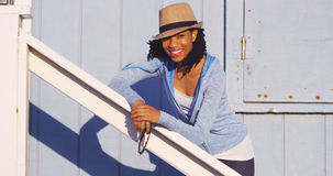Black woman leaning on wooden rail smiling Stock Image