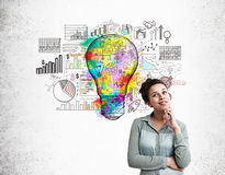 Black woman and light bulb sketch. Woman standing at concrete wall background with colorful light bulb drawn on it. Concept of new idea Stock Images