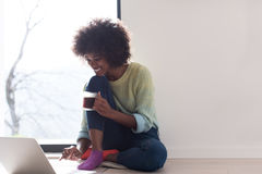 Black woman in the living room on the floor. Young african american woman smiling sitting on the floor near bright window while looking at open laptop computer Royalty Free Stock Image