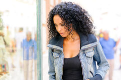 Black woman looking at the shop window. Portrait of an attractive black woman, afro hairstyle, looking at the shop window Stock Photography