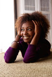 Black woman lying down on floor smiling Stock Images