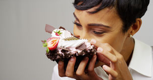 Black woman making a mess eating a huge fancy dessert Stock Photo