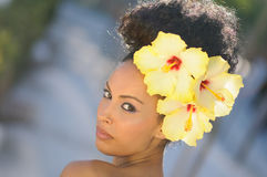 Black woman, model of fashion, with big flowers in her hair Royalty Free Stock Photos