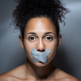Black woman with mouth covered with tape Stock Images