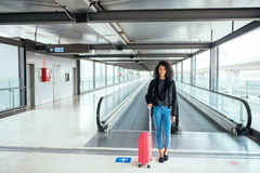 Black woman in the moving walkway at the airport with a pink sui Stock Photos