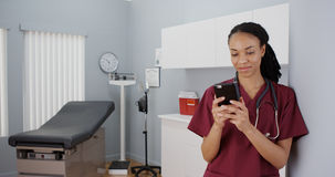 Black woman nurse texting on smartphone Royalty Free Stock Photography