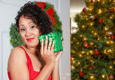 Black Woman Opening a Christmas present Stock Photo