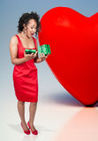 Black Woman Opening a Valentines present. A beautiful young black woman opening a Valentines Day present Stock Photo