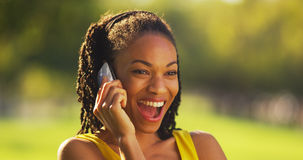 Black woman on the phone laughing outdoors Stock Photography
